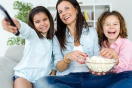 Portrait of beautiful mother and her daughters eating popcorns at home.